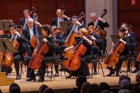 North Carolina Symphony musicians performing in the cello section, with double bassists visible behind them, onstage in Raleigh's Meymandi Concert Hall at the Duke Energy Center for the Performing Arts